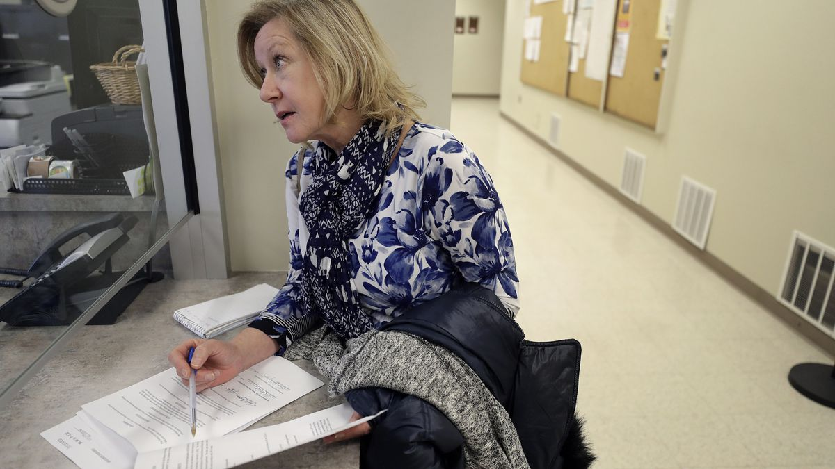 """In this Thursday, Jan. 16, 2020 photo Jo Goode, city hall reporter for The Herald News of Fall River, Mass., picks up documents, at Fall River City Hall. Goode, who had reported extensively on the Fall River mayor's indictment on federal extortion charges, didn't expect that in 2018 the mayor would create an anonymous website, with her name as the address, featuring an endless loop of a video clip of President Donald Trump saying """"You are fake news!"""" (AP Photo/Steven Senne)"""