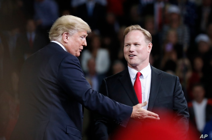 President Donald Trump talks with Republican candidate for Kansas' 2nd Congressional District Steve Watkins during a campaign rally at Kansas Expocentre, Oct. 6, 2018 in Topeka, Kan.