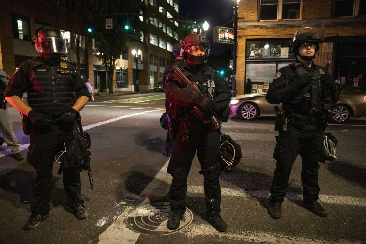 Portland police stand guard Saturday, Aug. 29, 2020, in Portland, Ore. One person was shot and killed late Saturday in Portland as a large caravan of President Donald Trump supporters and Black Lives Matter protesters clashed in the streets, police said. It wasna€™t clear if the shooting was linked to fights that broke out as a caravan of about 600 vehicles was confronted by protesters in the citya€™s downtown. (AP Photo/Paula Bronstein)