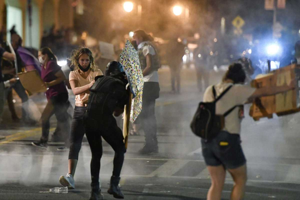 Protesters stand amid clouds of chemical irritant released by police outside the Public Safety Building in Rochester, N.Y., Thursday, Sept. 3, 2020. Seven police officers involved in the suffocation death of Daniel Prude in Rochester, New York, were suspended Thursday by the city's mayor, who said she was misled for months about the circumstances of the fatal encounter. (AP Photo/Adrian Kraus)