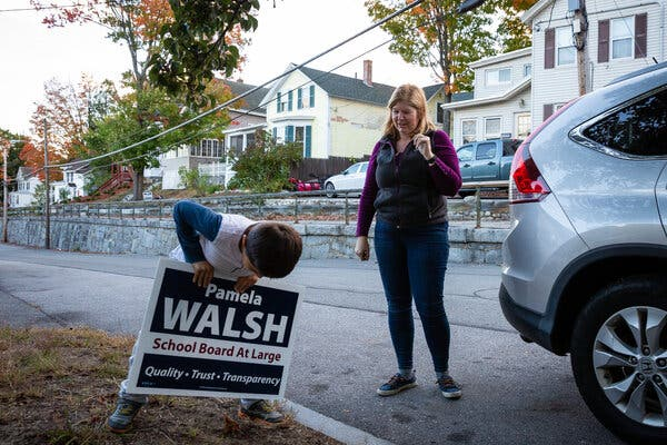 Pamela Walsh and her 7-year-old son, Luke, installed campaign signs in Concord, N.H., where Ms. Walsh is running for the school board.